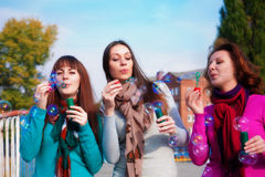 Three young beautiful women blow bubbles Stock Photo