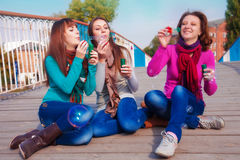 Three young beautiful women blow bubbles Royalty Free Stock Image