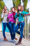 Three young beautiful women blow bubbles Stock Image