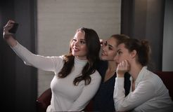Three young beautiful women sitting in a bar and doing a selfie royalty free stock photography