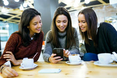 Three young beautiful women using mobile phone at cafe shop. Stock Photo