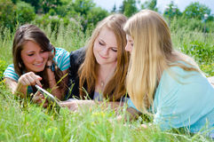 Three young blonde and brunette girls using tablet royalty free stock image