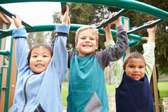 Three Young Boys On Climbing Frame In Playground Stock Photography