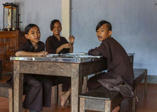 Three young boys monks studying in classroom at Royal Buddhist T Stock Images