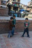Three young boys playing a game with a coin in the street, Kathmandu, Nepal, March 2014 royalty free stock image