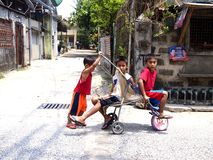 Three young boys playing with an improvised ride Stock Photo