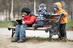 Three young boys playing on a park bench in winter Royalty Free Stock Image