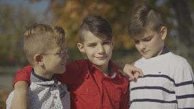 Three young boys smiling and hugging outdoors. Brothers spend time together. stock video footage