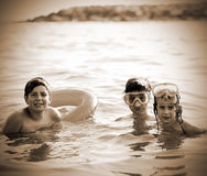 Three young brothers in the sea in summer Stock Photography