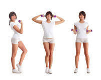 Three young brunette women holding dumbbells Royalty Free Stock Photos