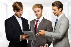 Three young businessman discussion about a something on a tablet Stock Image