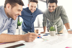 Three young businessmen leaning at table and working at project together Stock Photography