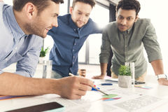 Three young businessmen leaning at table and working at project together Stock Photo