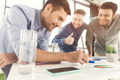 Three young businessmen leaning at table and working at project together Royalty Free Stock Photo