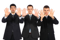 Three young businessmen show open palms Royalty Free Stock Image