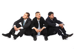 Three young businessmen sit on floor Royalty Free Stock Image