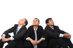 Three young businessmen sit on floor Stock Photo