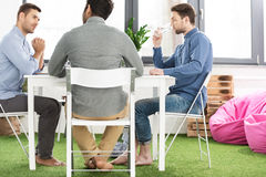 Three young businessmen sitting at table and working on new project together Stock Photos