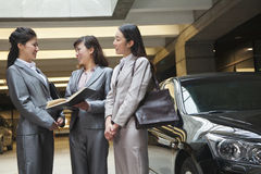 Three young businesswomen meeting and talking in parking garage Royalty Free Stock Photos