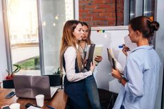 Three young businesswomen sharing new business ideas holding notes standing at whiteboard in office Royalty Free Stock Image