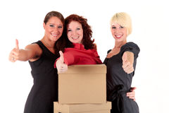 Three young businesswomen. Thumbs up. Three successful, young businesswomen hugging themselves and holding thumbs up. Studio shot. White background Royalty Free Stock Photo