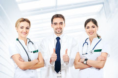 Three young Caucasian doctors in white clothes Stock Photography