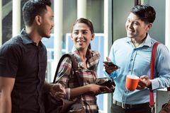 Three young and cheerful employees at their workplace talking in the morning Stock Images