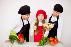 Three young chefs evaluate a salad isolated. Three young chefs near the white table evaluate a salad isolated Stock Images