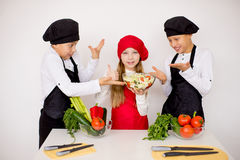 Three young chefs evaluate a salad isolated. Three young chefs near the white table evaluate a salad isolated. disgusting Royalty Free Stock Images