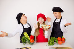 Three young chefs evaluate a salad isolated. Three young chefs near the white table evaluate a salad isolated. godlike Royalty Free Stock Photography