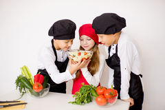 Three young chefs evaluate a salad isolated. Three young chefs near the white table evaluate a salad isolated. smell Stock Image