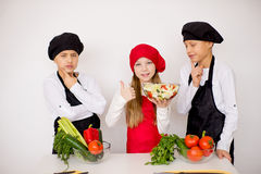 Three young chefs evaluate a salad isolated. Three young chefs near the white table evaluate a salad isolated. think Stock Photography