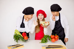 Three young chefs evaluate a salad isolated. Three young chefs near the white table evaluate a salad isolated. think Stock Image