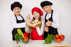 Three young chefs evaluate a salad isolated. Three young chefs near the white table evaluate a salad isolated. well done Stock Images