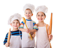 Three young chefs with ladle and rolling pin Royalty Free Stock Photography