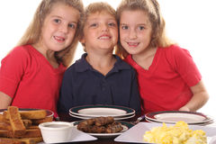 Three young children at breakfast. Shot of Three young children at breakfast Royalty Free Stock Images
