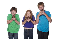 Three young children eating easter eggs. Three young children eating big easter eggs Stock Photo