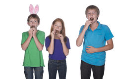 Three young children eating easter eggs. Three young children eating and stuffing their mouths with marshmallow chocolate easter eggs Stock Photography