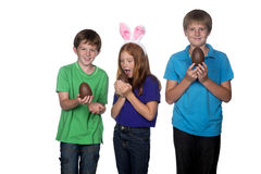 Three young children holding easter eggs. Three young children playing with large chocolate easter eggs Royalty Free Stock Images
