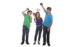 Three young children playing with easter eggs. Three young children playing with large chocolate easter eggs Royalty Free Stock Photos