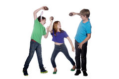 Three young children playing with easter eggs. Three young children playing with large chocolate easter eggs Royalty Free Stock Photography