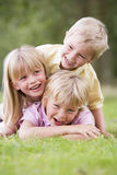 Three young children playing outdoors smiling Royalty Free Stock Images