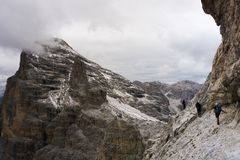 Three young climbers on an exposed Via Ferrata in the Dolomites. Young climbers on an exposed ledge of a Via Ferrata in the South Tyrol with a great view of the Stock Images