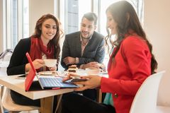 Three young colleagues relaxing during coffee break in a trendy cafeteria royalty free stock image