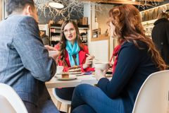 Three young colleagues relaxing during coffee break in a trendy cafeteria. Three young colleagues wearing smart casual outfits while relaxing during coffee break royalty free stock images