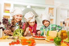 Three young cooks cutting pizza at the kitchen Royalty Free Stock Photos