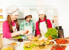 Three young cooks preparing hamburgers at kitchen Stock Photos