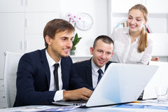 Three young coworkers working in company office Stock Images