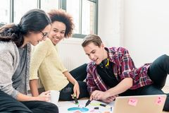 Three young creative employees working together on a project stock photo