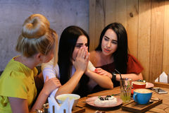 Three young cute girl girlfriends chatter, gossiping, share secr Stock Image